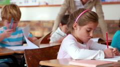 Schoolchildren colouring in books in classroom Stock Footage