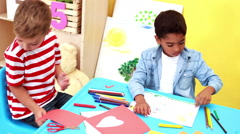 Cute little boys having art time in the classroom waving to camera - stock footage