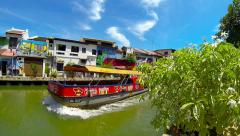 River and colorful buildings with tourist boat passing by. Melaka. Stock Footage