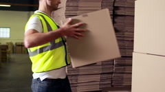 Warehouse worker stacking cardboard boxes Stock Footage