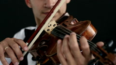 Violinist man playing the violin on a black background. Close up. Stock Footage