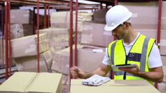 Warehouse worker checking boxes for shipping with tablet pc Stock Footage