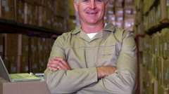 Warehouse worker smiling at camera with arms crossed Stock Footage