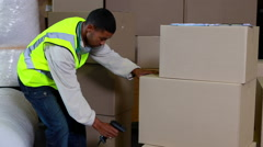 Warehouse worker scanning barcodes on boxes Stock Footage