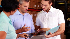Warehouse operatives discussing file on tablet pc - stock footage