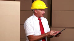 Warehouse manager sitting using his tablet pc Stock Footage