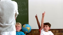 Cute pupils lifting their hands in classroom Stock Footage