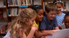 Cute pupils looking at laptop in the library - stock footage