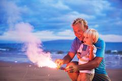 father and son lighting fireworks - stock photo