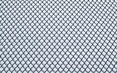 Frozen small chain-link fence pattern. - stock photo