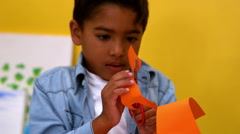 Cute little boy cutting paper shapes in classroom Stock Footage