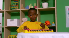 Cute little boy playing xylophone in classroom Stock Footage