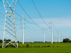 Stock Photo of high voltage power lines, green fields, sunny summer day.