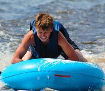 Boy tubing behind a boat Stock Photos