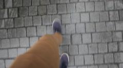 Male legs walk on wet sidewalk Stock Footage