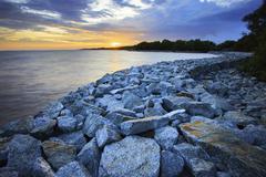 Sun set with rock dam sea coast bank protection perspective line Stock Photos