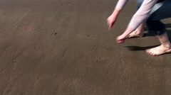 Girl drawing heart on the sand Stock Footage