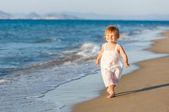Little girl walking on the beach Stock Photos