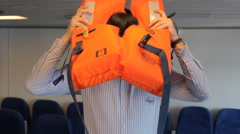 Man with black hair shows how to put on a lifejacket Stock Footage