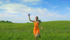 Happy young girl holding a paper plane and running, childhood, camera movement Stock Footage