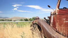 Stock Video Footage of Vintage rusty truck on a farm with mountains behind it