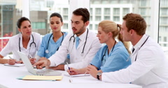 Medical team looking at laptop during meeting Stock Footage