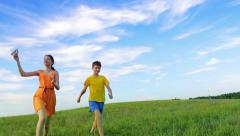 Two happy friends run with a paper airplane in the field, dreaming, future Stock Footage