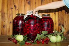 Hand and canned cherries Stock Photos