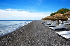 the beach with black volcanic stones at santorini island, greece - stock photo