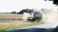 Combine harvesters and tractors harvesting a huge field Stock Footage