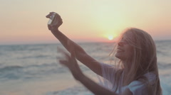 Lovely young girl doing self photo on the phone on the background of sunset by - stock footage