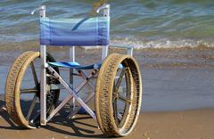 wheelchairs for disabled people on the beach - stock photo