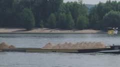 Sand ship navigating downstream river in front of river beach - medium shot Stock Footage