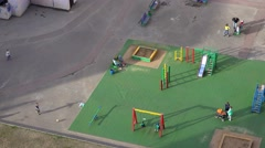 Children  play in inner yard playground of living buildings comlex on sunny day. Stock Footage