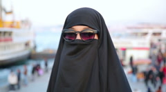 Steadycam - Woman with chador, hijab wearing sunglasses - stock footage