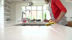 Slow Motion Sequence Of Woman Cleaning Surface In Kitchen Stock Footage