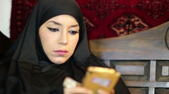 Woman with chador headscarf using mobile phone Stock Footage