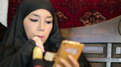 Woman with chador headscarf smoking shisha and using mobile phone Stock Footage