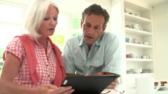 Middle Aged Couple Looking At Digital Tablet Having Argument - stock footage