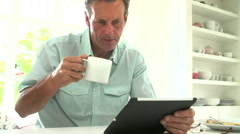 Middle Aged Man Looking At Digital Tablet Over Breakfast Stock Footage
