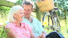 Middle Aged Couple Relaxing On Country Cycle Ride - stock footage