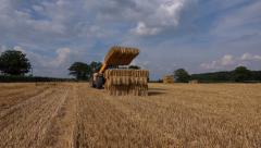 Agriculture farming tractor stacking bales of straw hay Stock Footage