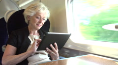 Businesswoman Commuting On Train Using Digital Tablet - stock footage