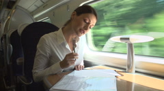 Female Commuter On Train Working On Document Stock Footage