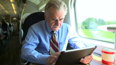 Senior Businessman Commuting On Train Using Digital Tablet Stock Footage