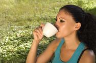 Stock Photo of beautiful girl with black hair drinking coffee