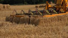 Agriculture farming tractor picking up bales of straw hay Stock Footage