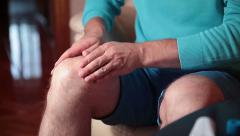 Man smears cream and massages injured knee. - stock footage