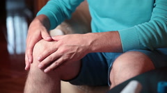Man massaging injured knee. - stock footage