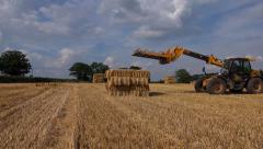 Timelapse Agriculture farming tractor picking up bales of straw hay Stock Footage